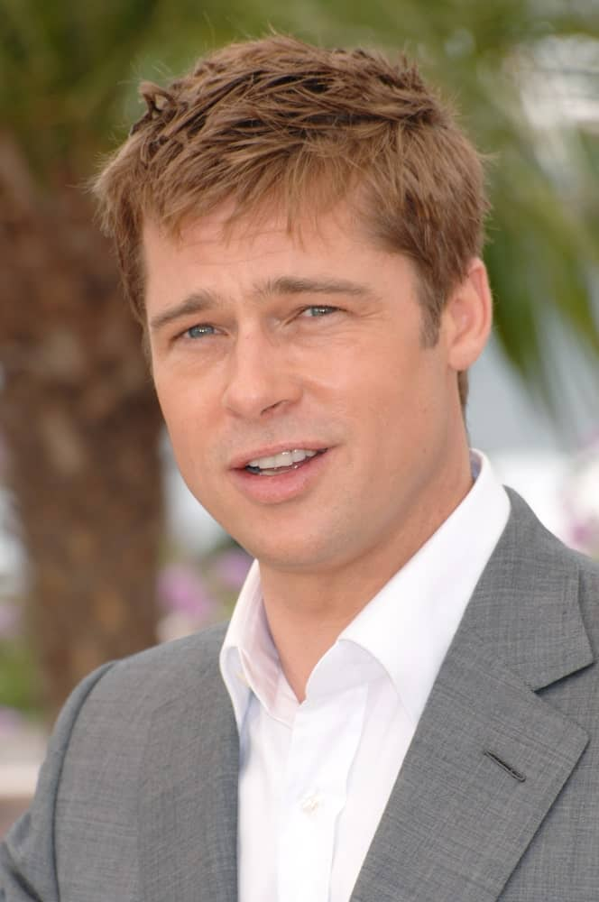 Brad Pitt in a white shirt with a gray blazer sporting a short hairstyle.