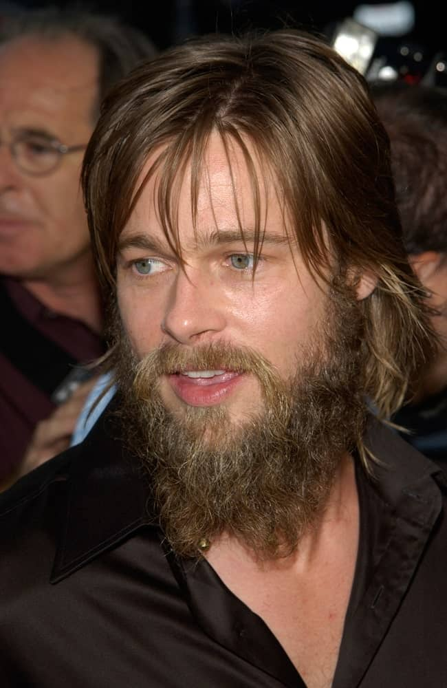 A long-haired Brad Pitt in a black shirt. He has a thick beard as well.