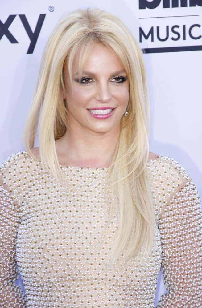 Britney Spears's simple layered straight loose hairstyle with choppy bangs creates a nice frame around her oval face at the 2015 Billboard Music Awards on May 17, 2015.