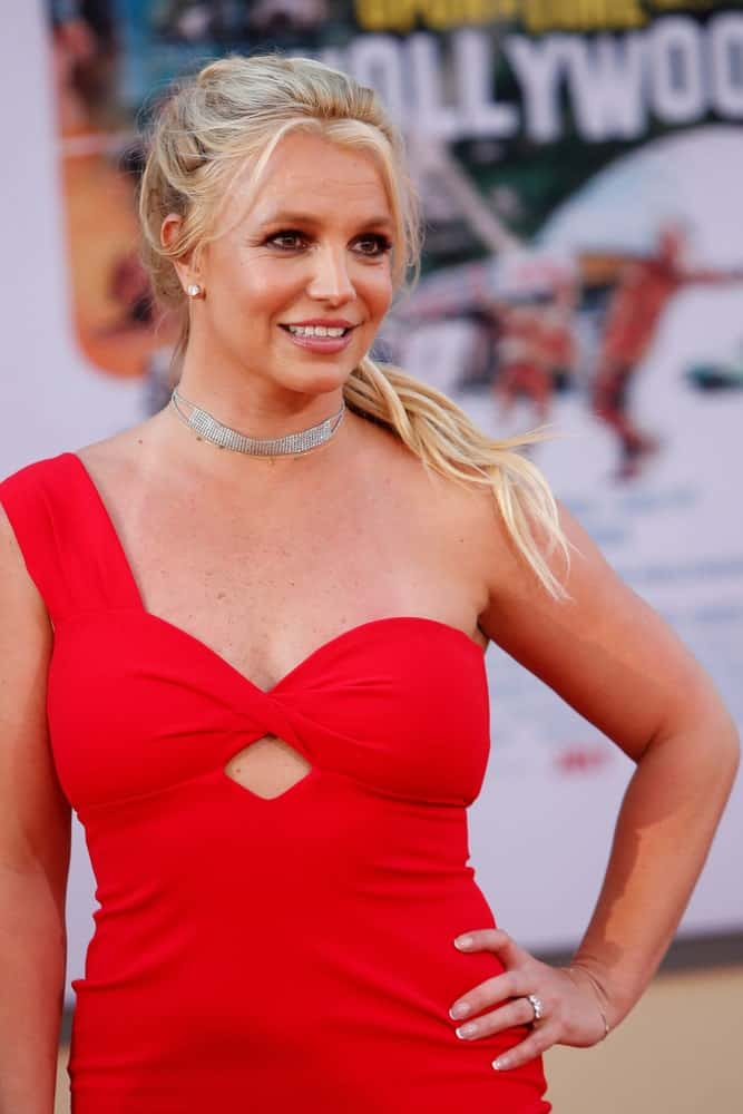 """Britney Spears gathered her long highlighted hair in a slick ponytail with curtain bangs at the """"Once Upon a Time in Hollywood"""" Premiere held on July 22, 2019."""