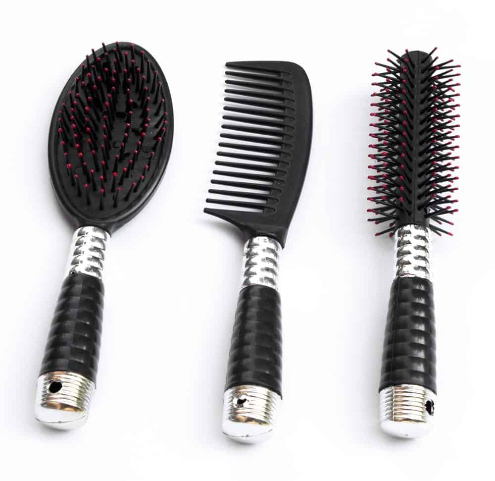 A focused look of a pair of hair brush and a comb on a white background.