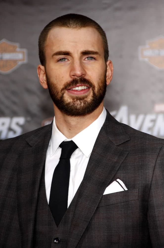 Chris Evans paired his buzz cut hairstyle with a scruffy full beard and a three-piece suit at the Los Angeles premiere of