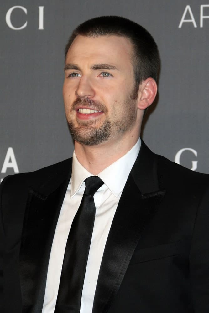 Chris Evans attended the LACMA 2012 Art + Film Gala at Los Angeles County Musem of Art on October 27, 2012 in Los Angeles, CA. He wore a black suit to go with his buzz cut hairstyle and goatee.