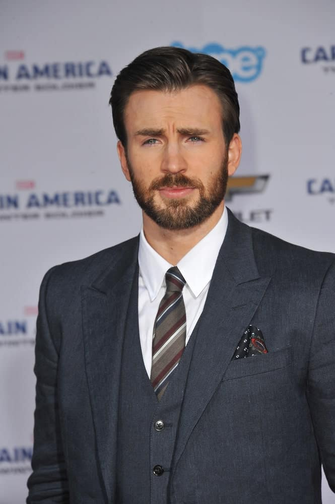 On March 13, 2014, Chris Evans wore a classy three-piece suit with his dark side-parted slick hairstyle at the world premiere of his movie