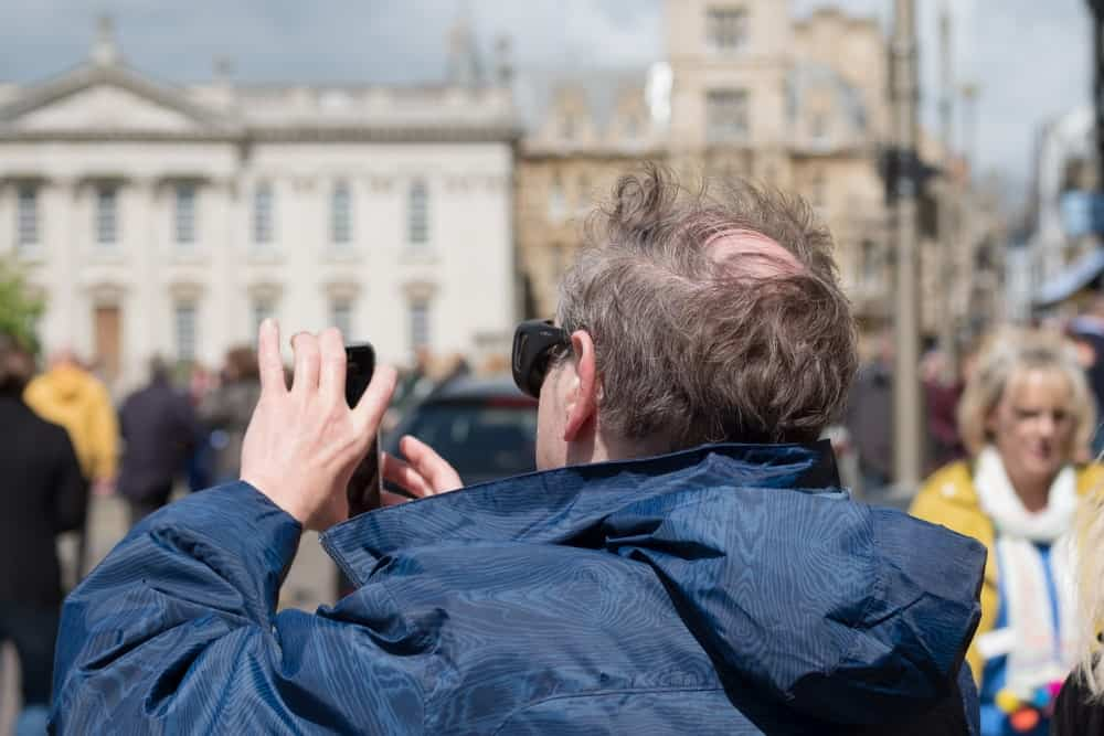 A comb over hairstyle of a man in a navy blue jacket, taking a photo in Cambridge, UK.