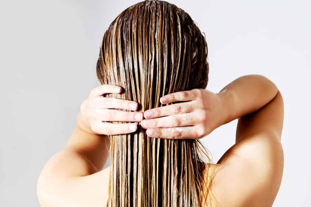 Woman applying hair conditioner.