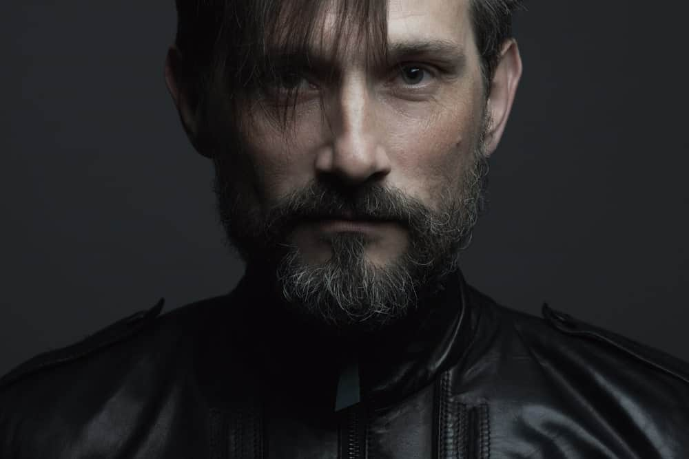 A 40 year-old man in a black leather jacket, flaunting a fabulous fringe cut.