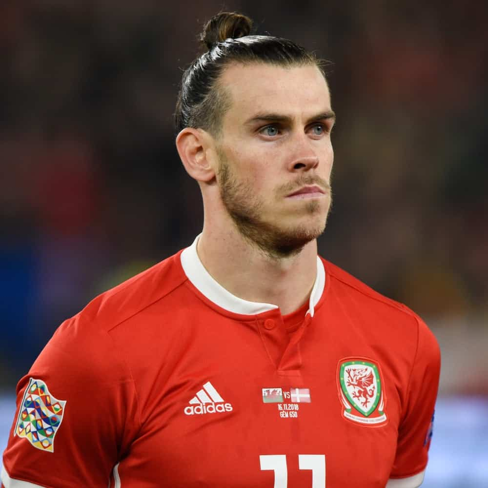 The speedy Midfielder of Real Madrid, Gareth Bale sporting his signature man bun hairstyle during a match between Wales national team where Bale plays and Denmark national football team.