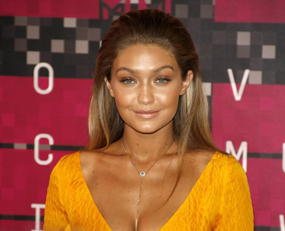 A bronzed Gigi Hadid wore a sexy yellow dress to pair with her brushed back half up hairstyle and bright smile at the 2015 MTV Video Music Awards held at the Microsoft Theater in Los Angeles on August 30, 2015.
