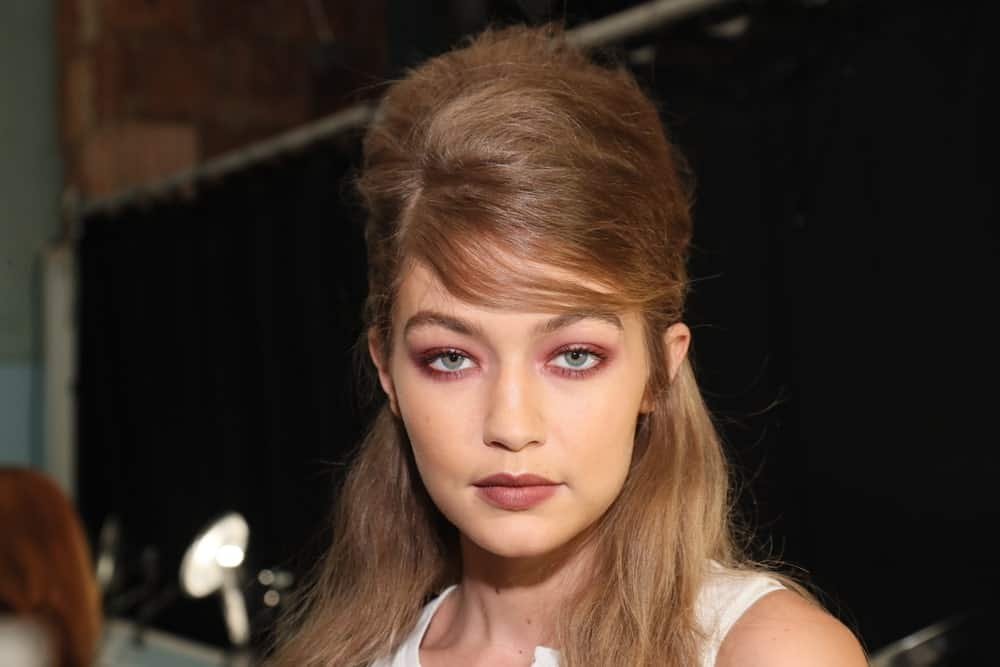 Gigi Hadid was at the backstage before the Anna Sui Spring 2017 Fashion Show on September 14, 2016 in New York City. Her hair was styled to a unique half up hairstyle with a beehive finish.