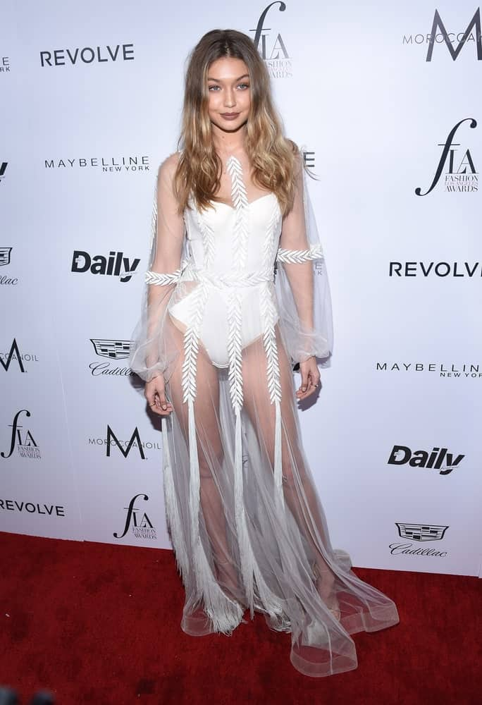 Gigi Hadid looked stunning in her white sheer outfit and loose wavy balayage hairstyle parted in the middle at the 2nd Annual Fashion Los Angeles Awards on March 20, 2016 in Hollywood, CA.