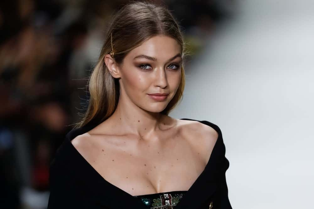 Gigi Hadid flashed her lovely smile with her pinned half up hairstyle when she walked the runway at the Versace show during Milan Fashion Week Spring/Summer 2018 on September 22, 2017 in Milan, Italy.