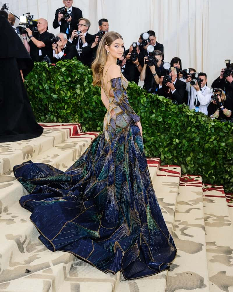 Gigi Hadid attended the 2018 Metropolitan Museum of Art Costume Institute Gala with the theme, Heavenly Bodies: Fashion and the Catholic Imagination. She came in a beautiful and colorful long gown with her ombre hair in a half up pinned hairstyle.