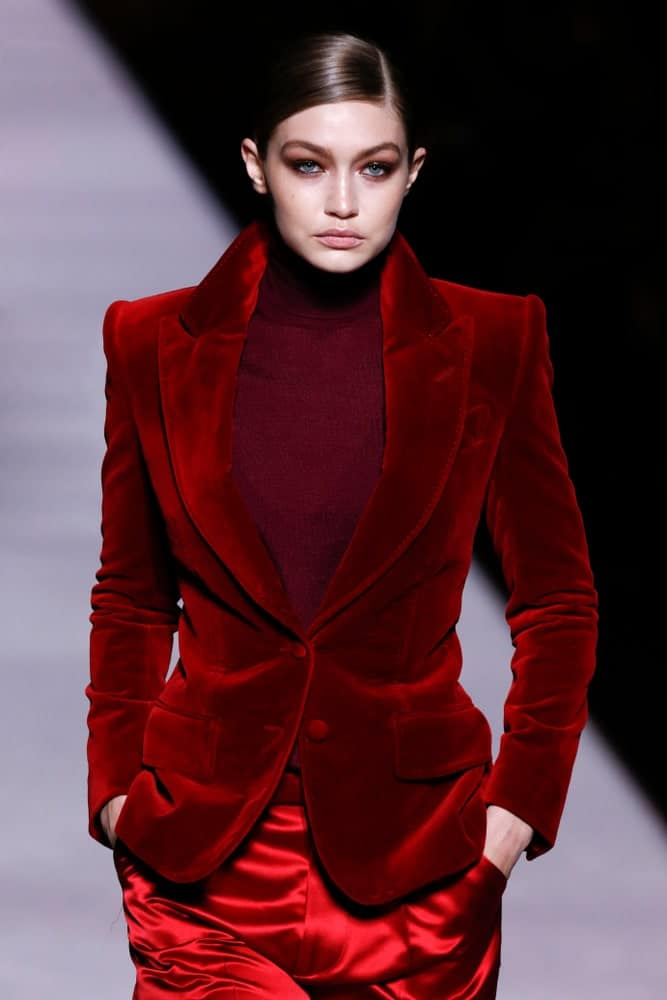 On February 06, 2019, Gigi Hadid walked the runway at Tom Ford Fall Winter 2019 Fashion Show at Park Avenue Armory in New York. She was dressed in a red velvet jacket with her hair in a slick low bun hairstyle.