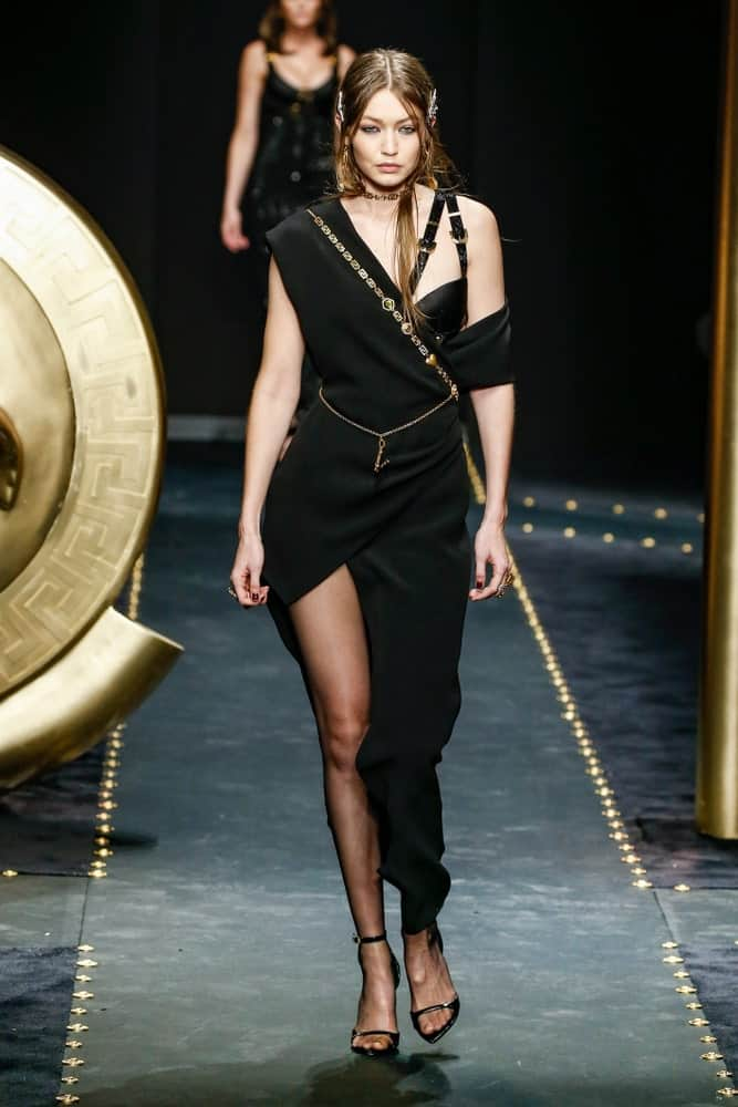 Gigi Hadid walked the runway at the Versace show at Milan Fashion Week Autumn/Winter 2019/20 on February 22, 2019 in Milan, Italy. She was dressed in a goddess-like black dress and her hair was pinned into a half-up hairstyle.