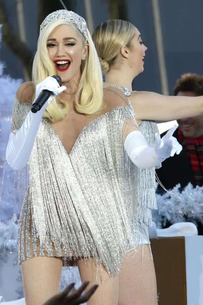Gwen Stefani wore a dazzling short dress during the Macy's Thanksgiving Day Parade in Bryant Park on November 21, 2017. Her long side-swept hairstyle was incorporated with a sparkly headband and had curls at the tips.