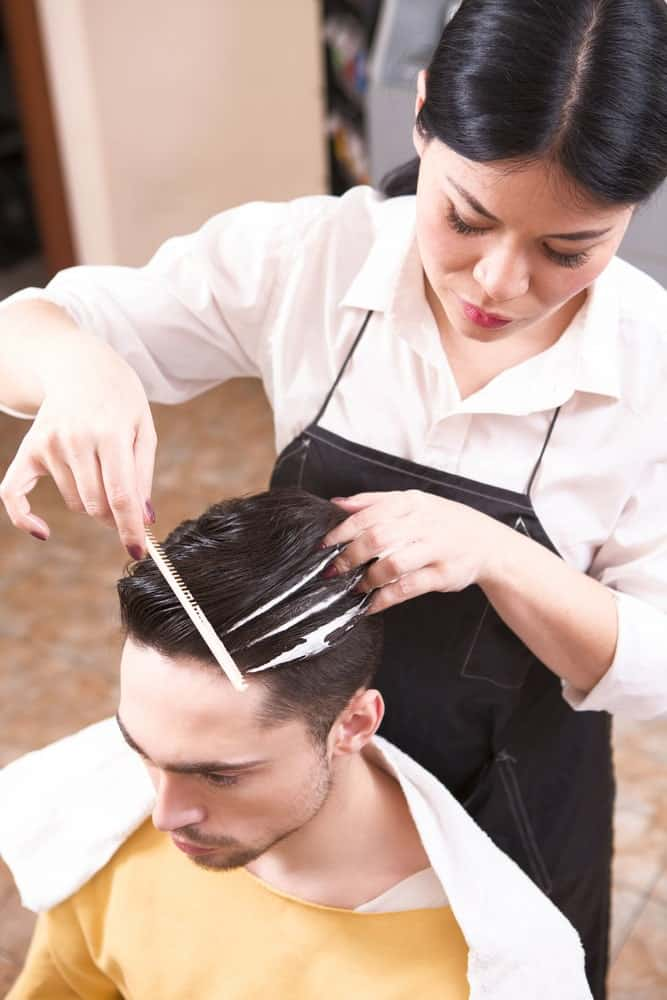 Hairdresser styling man's hair with a comb and mousse.