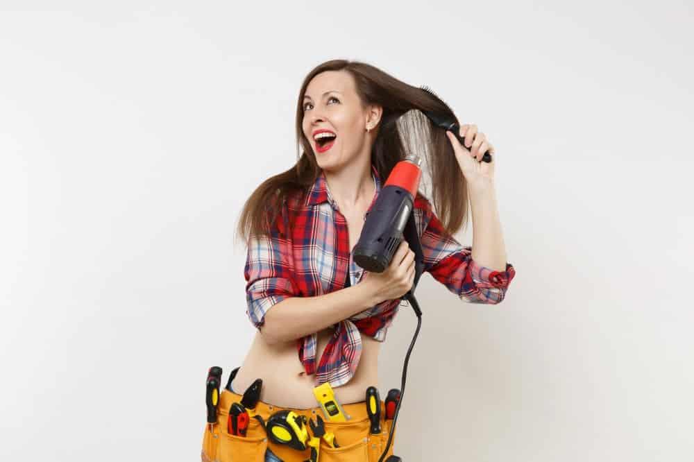 Heat Gun Vs Hair Dryer. A woman using a heat gun on her hair.