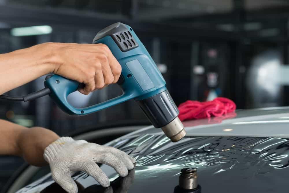 Heat Gun Vs Hair Dryer. A heat gun being used to apply car window tint.