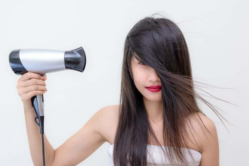 Heat Gun Vs Hair Dryer. A woman using a hair dryer on her long dark hair.