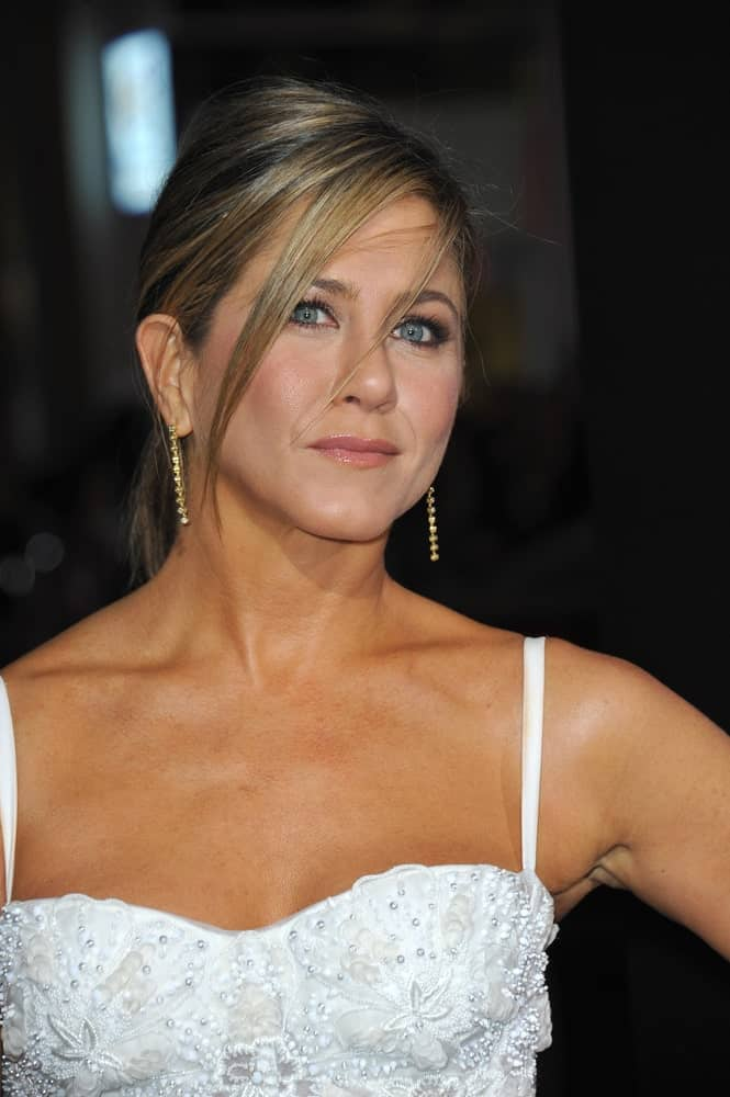 """Jennifer Aniston's blonde locks were arranged into a sleek ponytail with long side bangs at the Los Angeles premiere of her movie """"Horrible Bosses 2"""" on November 20, 2014. She finished the look with gold dangling earrings and a white bodice dress inlaid with floral embellishments."""