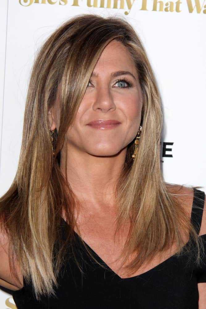 "Jennifer Aniston flaunting her blonde side-parted hair incorporated with long side bangs that almost covered the side part of her face. This was taken at the ""She's Funny That Way"" Red Carpet Premiere 2015 held last August 19th."
