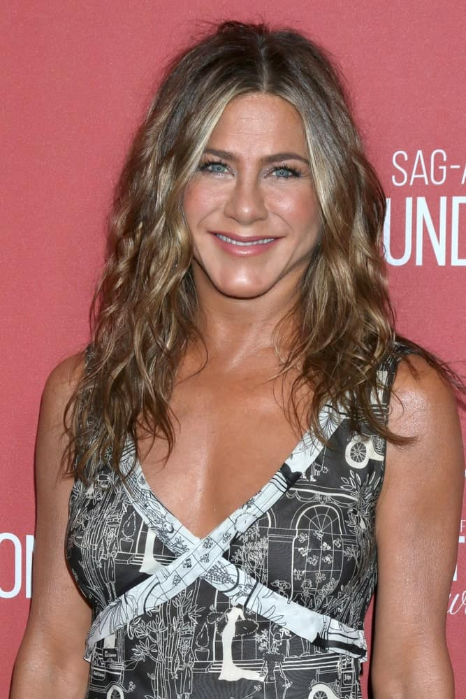 Jennifer Aniston showing off her permed beach waves paired with a black printed dress during the 4th Annual Patron of the Artists Awards on November 7, 2019.