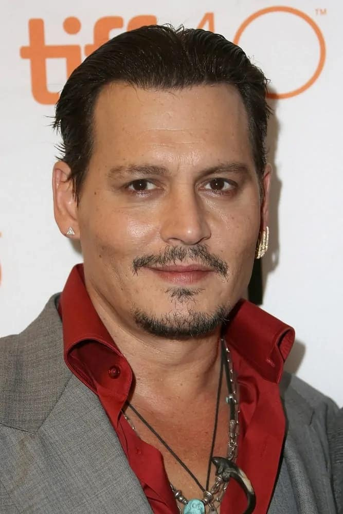 """Actor Johnny Depp had his usually messy hair slicked back into this raven masterpiece paired with mismatched earrings and some necklaces during the """"Black Mass"""" premiere at the 2015 Toronto International Film Festival last September 14, 2015, in Toronto, Canada."""