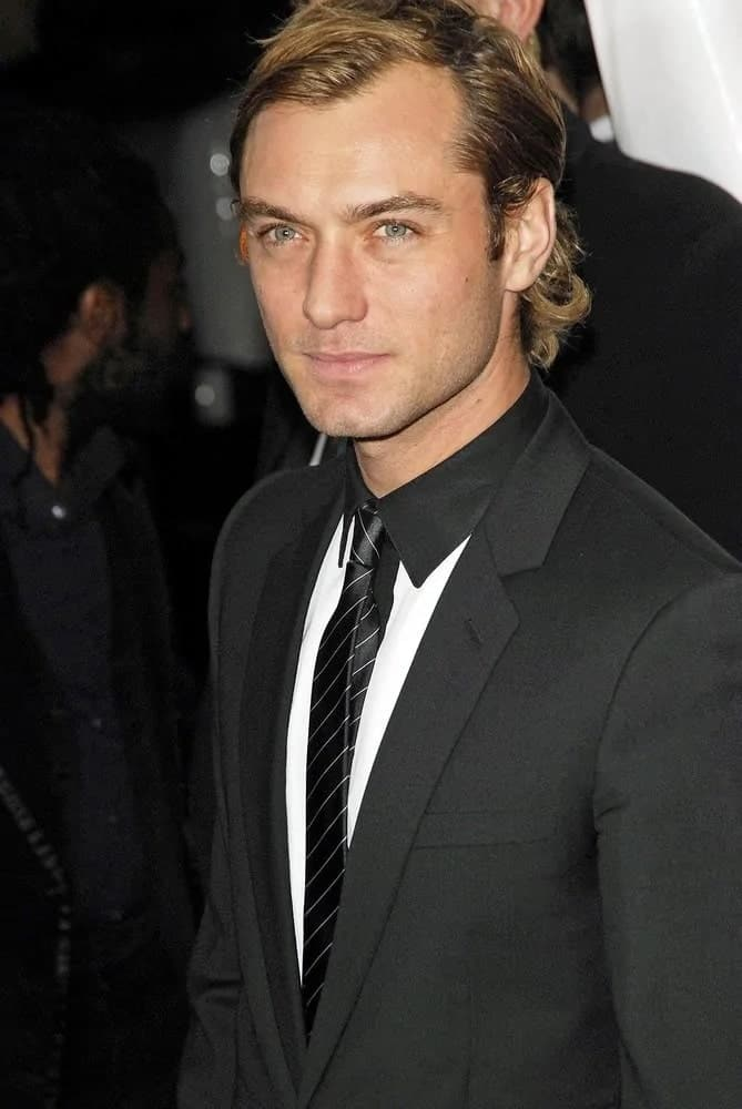 """Actor Jude Law looked absolutely gorgeous with his medium-length side-parted hairstyle with some curls flipping at the tips of his hair when he attended the New York premiere of """"The Holiday"""" in 2006."""