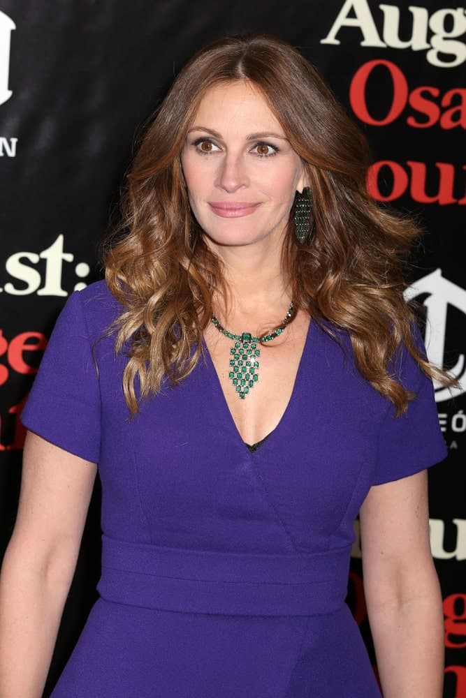 """Julia Roberts exhibited a charming aura with her center-parted waves at the premiere of """"August: Osage County"""" at the Ziegfeld Theater on December 12, 2013. She finished the look with a blue V-neck dress along with a matching necklace and earrings."""