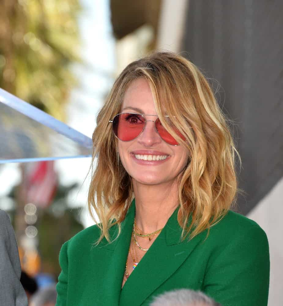 Julia Roberts looked sharp in a green suit incorporated with red shades and her highlighted beach waves during the Hollywood Walk of Fame Star Ceremony honoring actress Rita Wilson on March 29, 2019.