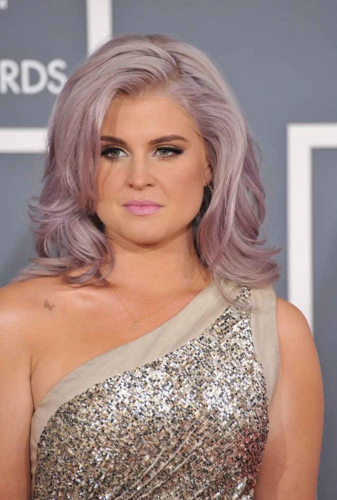 Kelly Osbourne with a purple hairstyle and a single shoulder gold dress, appearing at the 54th Annual Grammy Awards at the Staples Centre, Los Angeles, February 12, 2012.