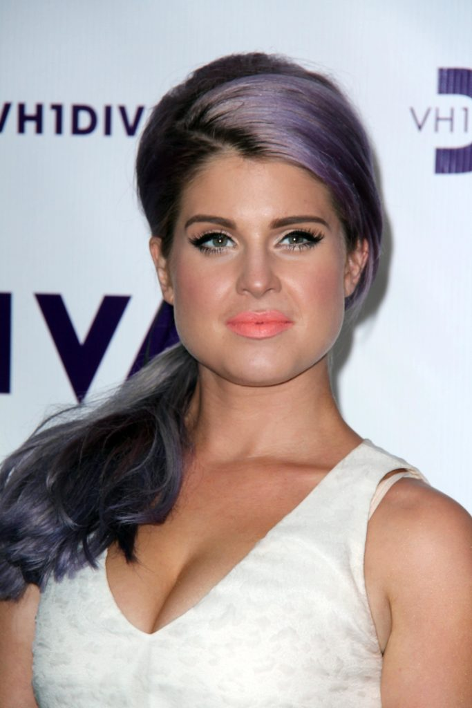 Kelly Osbourne on 16th of December 2012, sporting a long purple hair in a ponytail with bangs swept aside.