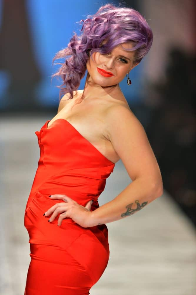 Kelly Osbourne looking stunning with the purple hair and the red dress. She's posing on the runway at The Heart Truth's Red Dress Collection on the 6th of February 2013.