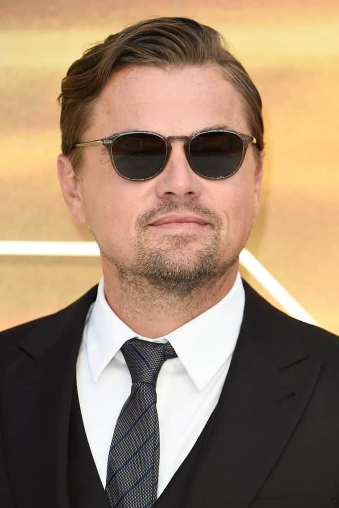 """Leonardo DiCaprio paired his wavy side-swept with a goatee at the UK premiere for """"Once Upon A Time In Hollywood"""" last July 30, 2019. Black shades and suit completed the sleek look."""
