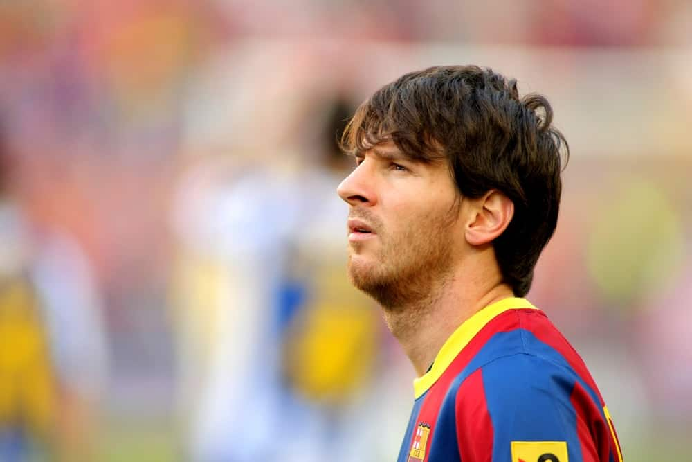 Lionel Messi of FC Barcelona looked at the scoreboard during the match between FC Barcelona and RCD Espanyol at the Nou Camp Stadium on May 8, 2011, in Barcelona, Spain. He paired his red and blue uniform with a long fringe hairstyle.