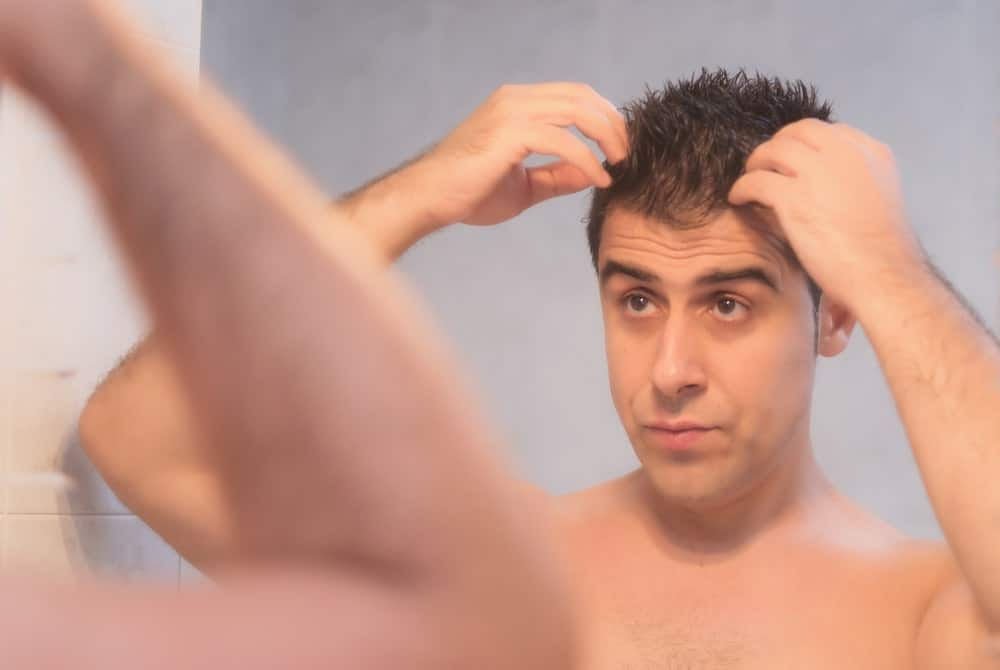 Man applying hair gel.