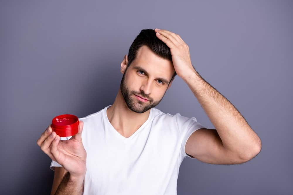 Man applying hair wax to his black hair.