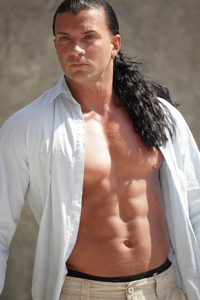 A young man with long ponytail wears an open shirt that shows off his chiseled chest.