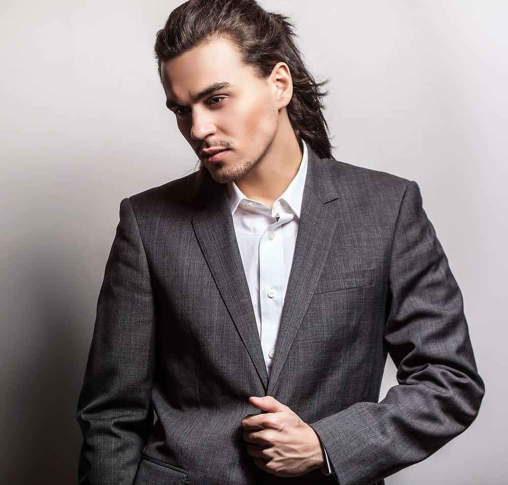 Young man rocks a ponytail hairstyle with a tuxedo.
