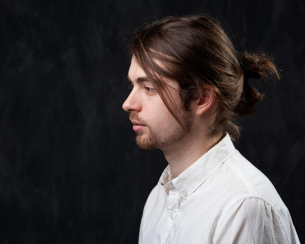 Side profile of a young man with mustache, fringe and a ponytail.