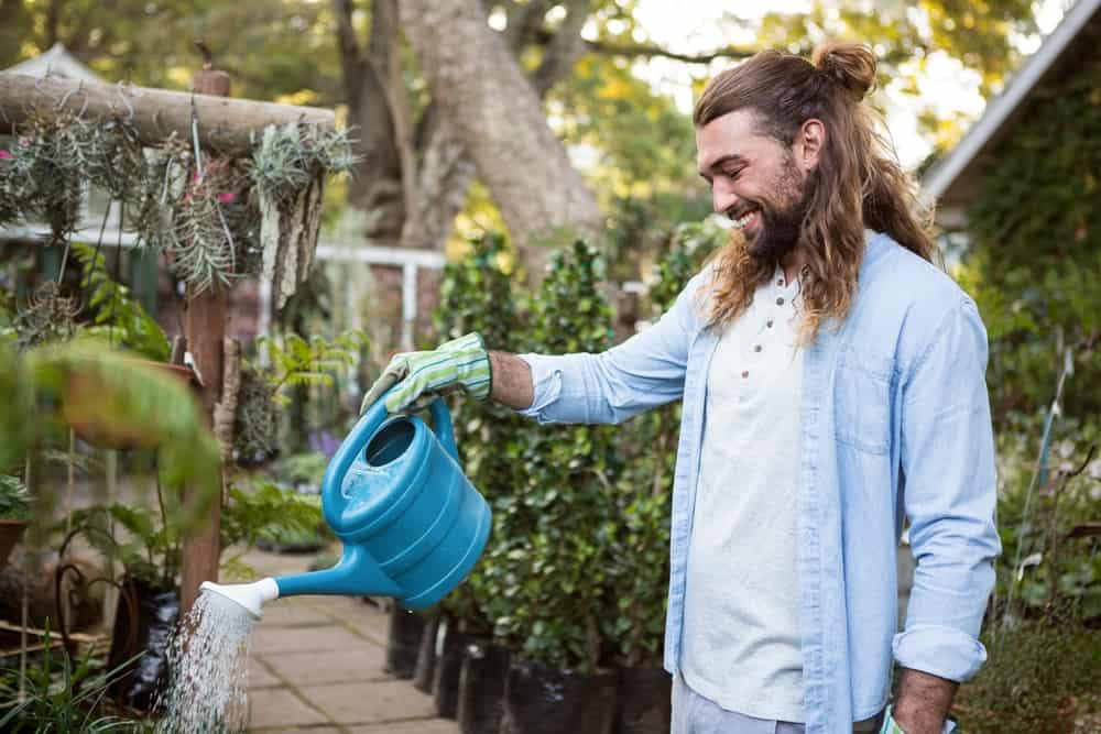 The man smiles while watering the plants in the garden.