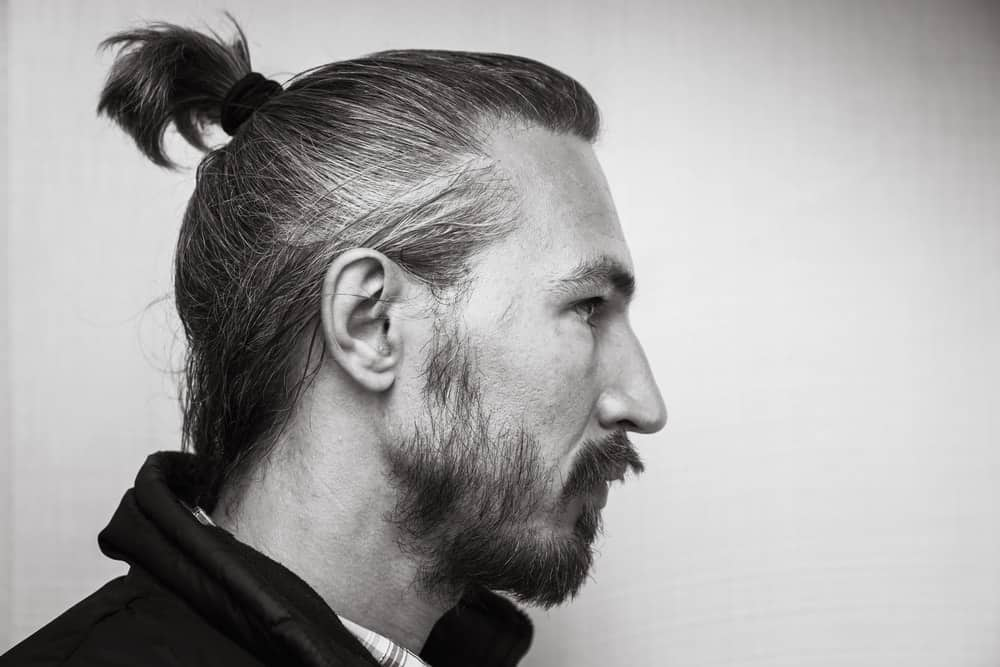 Side profile of a man with ponytail and beard.
