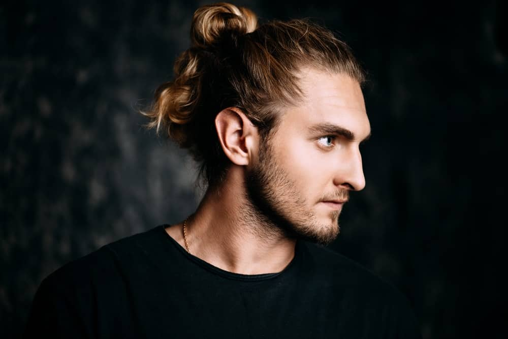 Side profile of a blonde man sporting a ponytail hairstyle.