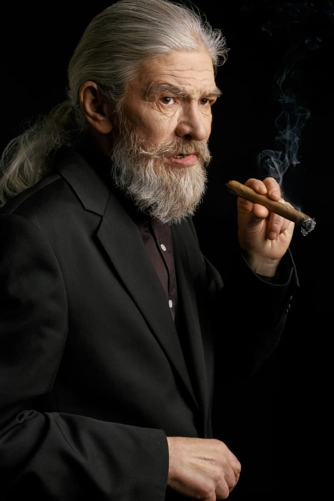A white-haired old man rocks a ponytail and beard while smoking cigar.
