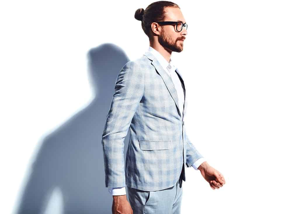 A look at a young businessman in a plaid blazer covering the white inner shirt on a white background with his shadow showing up. He has a beard and a man bun hairstyle, along with an eyeglasses.