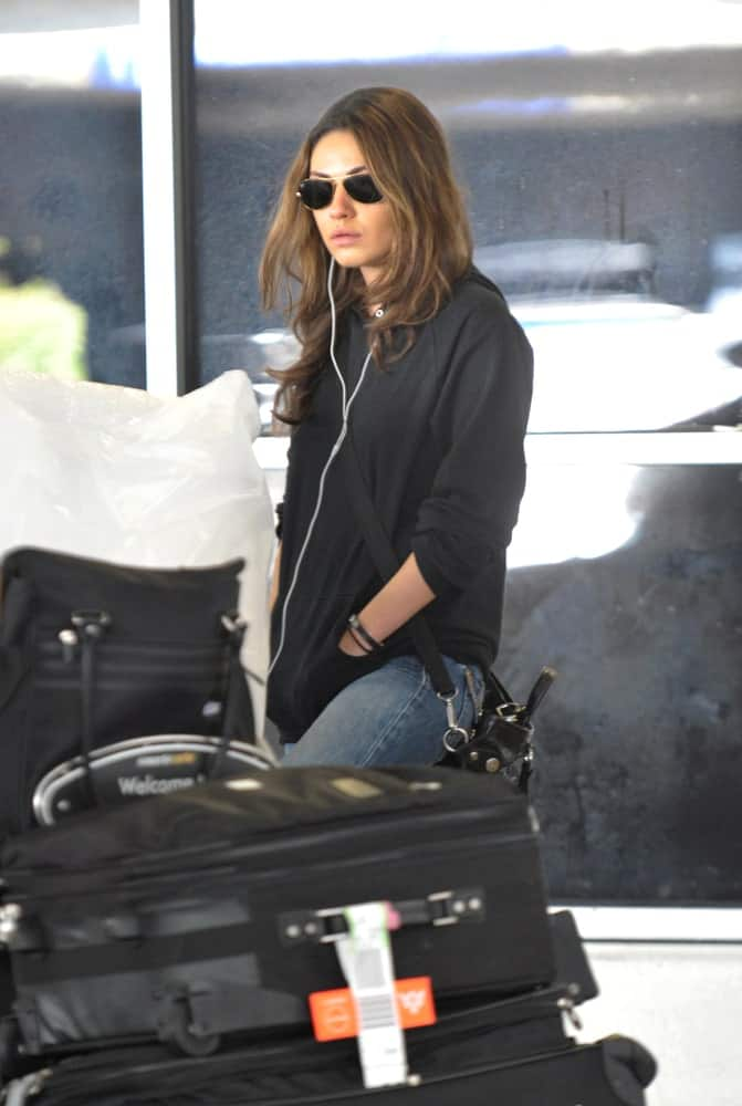 The actress Mila Kunis was seen at LAX last October 23, 2010 in Los Angeles, California. She opted for a casual black hoodie jacket paired with a reddish brown dyed loose tousled hair.
