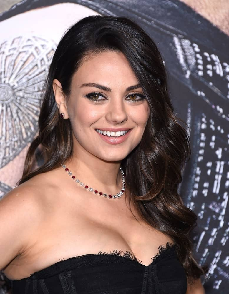 """Mila Kunis arrived at the """"Jupiter Ascending"""" Los Angeles Premiere last February 2, 2015 in Hollywood wearing a strapless black dress to complement her medium-length side-swept bangs that has subtle highlights."""