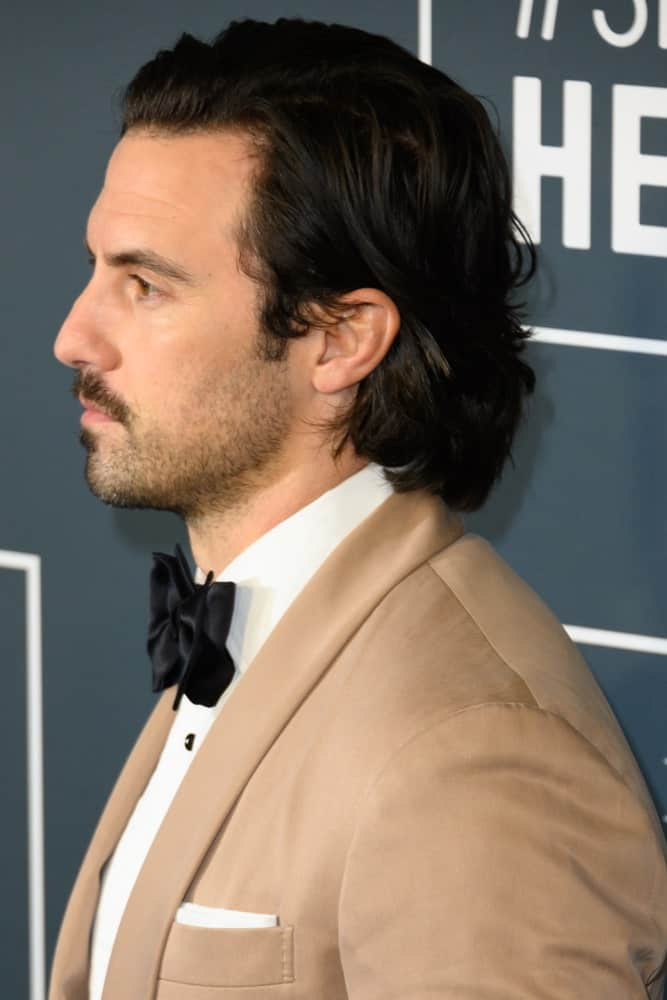 Milo Ventimiglia appeared with a neat wavy style showing off his black hair and beard during the 25th Annual Critics' Choice Awards at Barker Hangar on January 12, 2020.