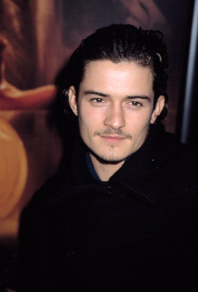Orlando Bloom has thin trimmed beard that went quite well with his long dark curly hairstyle that was brushed back  into a slick finish at the 2002 premiere of
